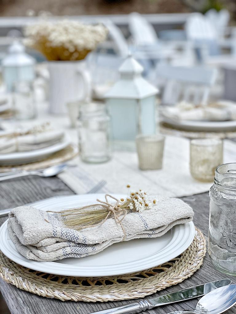 Welcome Home Saturday vom beliebten Lifestyle-Blog She Gave It A Go: Bild einer Tischdekoration mit einem gewebten Tellerladegerät, einem weißen Keramikteller und einer Leinenserviette, die mit Zwilling und etwas Kamille gebunden ist.